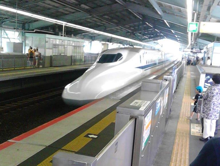 Ein Shinkansen fährt in einen Bahnhof ein.