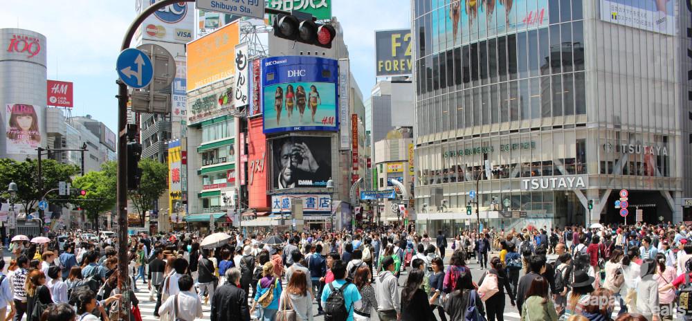 Die berühmte Shibuya Crossing mit bekannten Läden und vielen Besuchern.