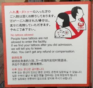 Foto des Hinweisschilds zum Verbot des Badens mit Tätowierungen.