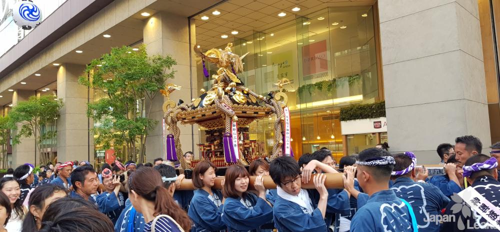 Foto einer Mikoshi-Parade im Rahmen eines Schreinfestes.