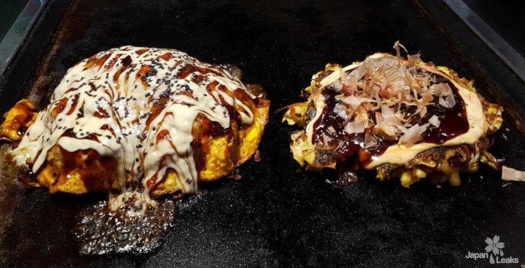 Foto von 2 Okonomiyaki auf einer heißen Platte.
